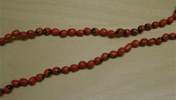 Halsband av tvåfärgade bönor, rött och lite svart.